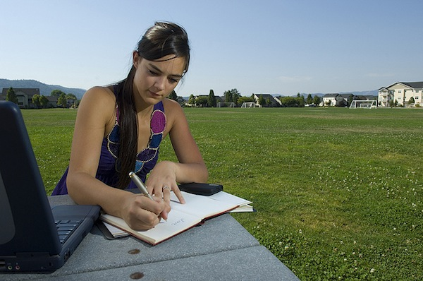 College Student studying in park with Laptop